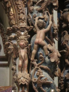 Decorative carvings of a naked cherub climbing a vine.