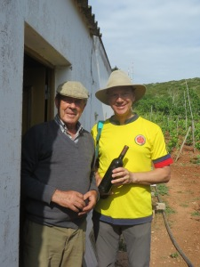 Two men stand just outside a doorway to a white stucco building that has a rippled tile roof peeking over the side. The building and the men are in a vineyard with bare earth at their feet and grapevines in the background. The man on the right holds an unlabeled bottle of wine that he is purchasing from the other man. The buyer has on a wide brimmed khaki hiking hat, a bright yellow soccer shirt and grey hiking pants. The seller is wearing a traditional light brown newsboy style cap, a grey sweater with a collared shirt underneath, and khaki pants. Both men are smiling.