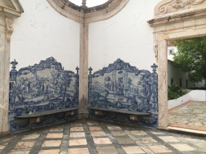 The outdoor room has a marble tiled floor with square pink tiles and grey rectangular border tiles. We are looking into the corner of the room and on walls adjacent to the corner are stone benches surrounded by blue and white Portuguese tile work. The tiles are painted and glazed with medieval scenes. The tiles have a decorative edge and crosses atop the right and left sides of the tile picture. On each outer side of the benches is an open entry surrounded by pink marble. Though the right doorway we can see a tree and shrubs.