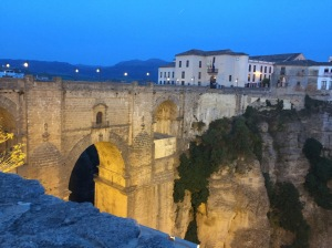 The Puente Nuevo (new bridge) in Ronda, Spain, is made of brick and spans a crevasse with a small river below. The bridge has a large, high arch. We are looking at the bridge from the west side of it. On the other side of the crevasse is a white and grey cliff with shrubs in patches. Above, on the other side of the bridge, are white three-story buildings with grey roofs. There are mountains in the distance.