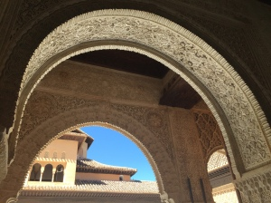 Looking through a Moorish carved stone double arch at the Alhambra. The carvings are intricate, with floral designs bordered by striped graphics. In the background is a tile-roofed building with a dormer and pink walls. The sky is a bright blue contrast.