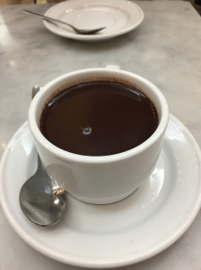 A white coffee cup with saucer and spoon on the left of the cup. The cup is filled with thick hot chocolate. The table is white and grey marble and there is another white plate and spoon in the background.