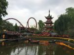 Tivoli Gardens is an amusement park. At the front of the scene is a man-made pond surrounded by shrubs and yellow flowers. There are three rowboats on the pond with a person in each boat. Beyond the pond is a roller coaster with a loop. To the right of the roller coaster is an Asian pagoda. Trees frame the photo on each side.