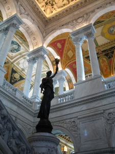 Statue of female on stairway pedestal inside the Great Hall of the Library of Congress Jefferson Building, with painted ceiling above and marble columns.