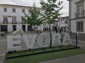 Sign spelling out Evora in town square with white buildings surrounding and trees in the square.