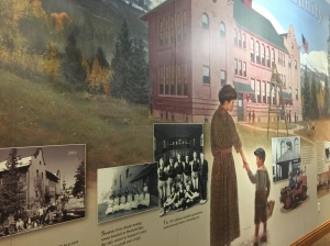 Mural with painting of early twentieth century woman holding young boy's hand in front of building that has become the library in Breckenridge. Mural includes old photographs of a group of students, young male athletes and of the building.