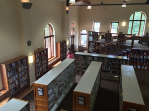 Interior of the Summit County Library South Branch in Breckenridge, Colorado, showing rows of shelves of the book collection, with seating on a raised area at the back of the room. Windows line the walls and the ceiling is very high, about 2 stories above the floor of the library. A female librarian talks with a man standing in the middle of the room.