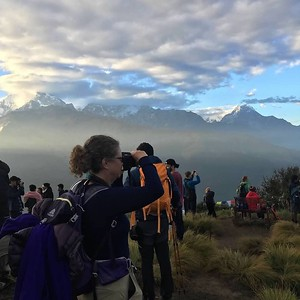 Laura holds an SLR camera up to take a photo on Poon Hill in Nepal. In the background are other trekkers and beyond then are snowcapped Himalayan mountains. Clouds are overhead, but there is a blue sky off to the right.